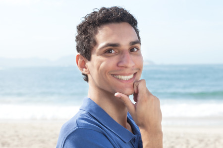 face to  face: Handsome argentinian guy at beach Stock Photo