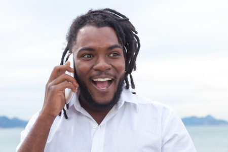 jamaican adult: Laughing african american guy with dreadlocks and white shirt at phone