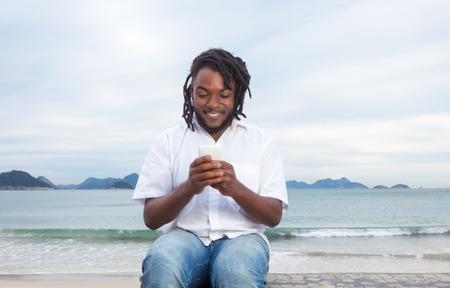 online bidding: African american guy with dreadlocks and white shirt typing message Stock Photo