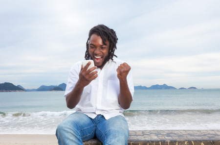 African american guy with dreadlocks and white shirt receiving good news Stock Photo