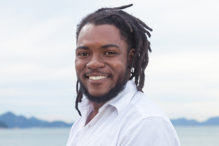 rastafari: Laughing african american guy with dreadlocks and white shirt Stock Photo
