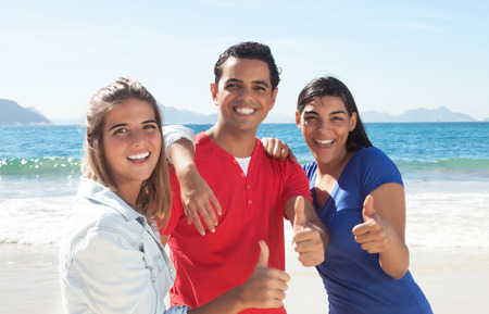 young people party: Group of three happy latin people at beach