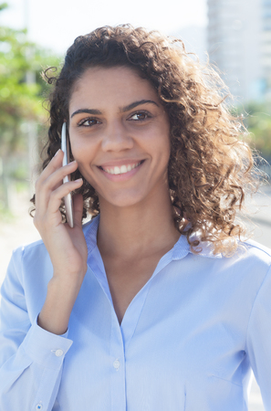 latina america: Laughing latin woman with blue blouse at phone in the city Stock Photo