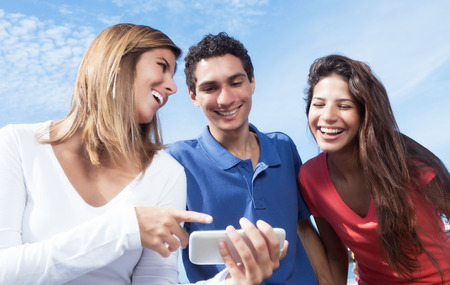 Group of young people showing at pictures on smartphone Stockfoto