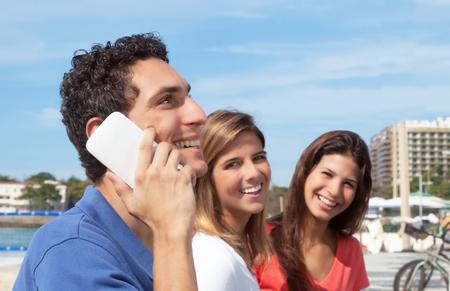 personas mirando: Chico mexicano ri�ndose de tel�fono con dos amigas en el fondo