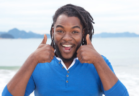 cheer: Funny african american guy with dreadlocks at beach
