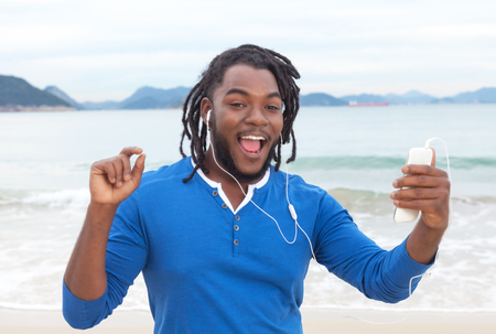 south american: African american guy with dreadlocks dancing at beach Stock Photo