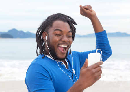 jamaican adult: African american guy with dreadlocks listening to music at beach