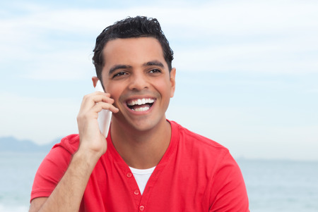 powerful man: Laughing latin guy at beach happy at phone Stock Photo