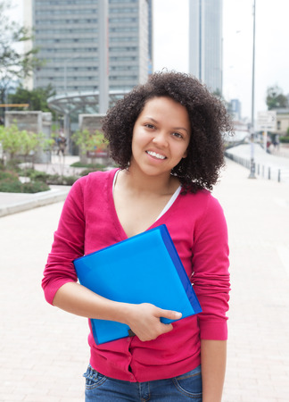 african student: African american female student standing in the city