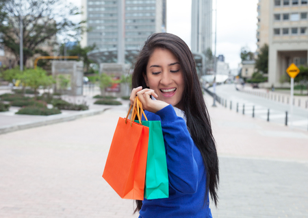 latina america: Happy latin woman with shopping bags in the city Stock Photo
