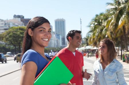 Latin vrouwelijke student met vrienden in de stad