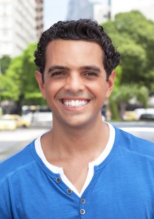 caras: Riendo chico latino en la ciudad mirando a la c�mara Foto de archivo