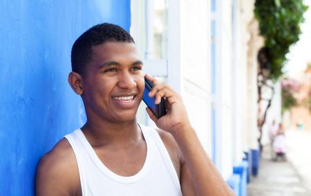 Latijnse man praten aan de telefoon in de voorkant van een blauwe muur