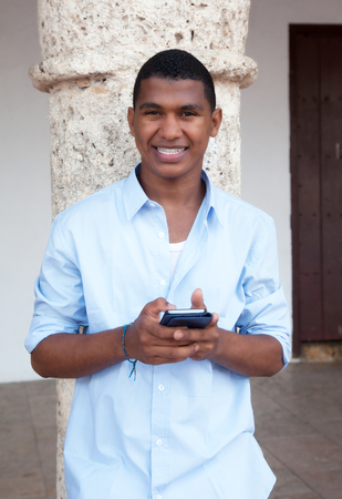 latin american: Young guy in a blue shirt typing message at phone Stock Photo