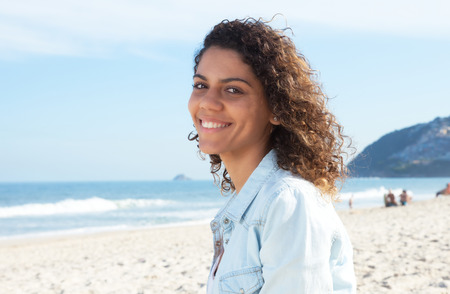 Laughing: Laughing latin woman with curly hair at beach Stock Photo