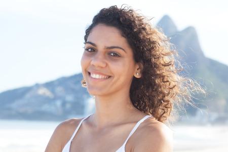latina america: Laughing latin woman with curly hair at beach at Rio de Janeiro Stock Photo