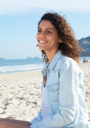latina america: Cute latin woman with curly hair dreaming at beach Stock Photo
