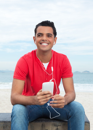 american downloads: Latin guy in red shirt listening music with phone