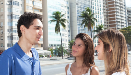 latina america: Young mexican guy talking with two girlfriends in the city