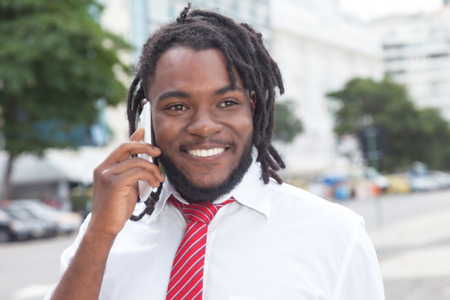 rastafari: African american businessman with dreadlocks at phone in the city
