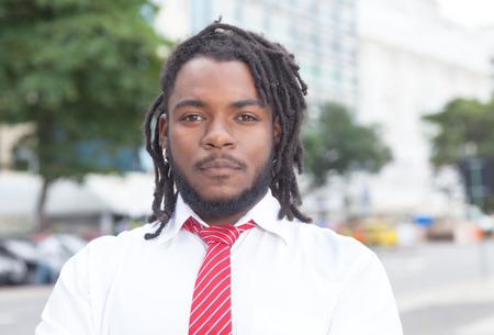 rastafari: Smart african american businessman with dreadlocks in the city Stock Photo