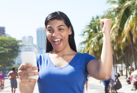 bidding: Attractive latin woman receiving good news on cellphone