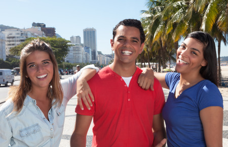 Group of three happy latin people in the city