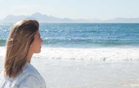 latina america: Blonde woman at beach looking thoughtful to the ocean
