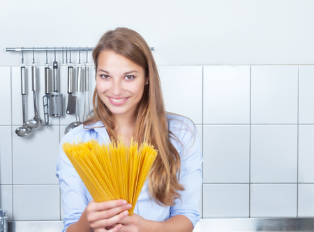 pasta: Laughing blonde woman with spaghetti at kitchen
