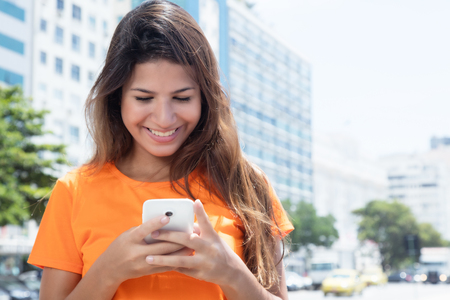 Lachende Kaukasische vrouw het typen bericht met telefoon Stockfoto