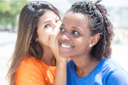 south american: Whispering girlfriends in the city Stock Photo