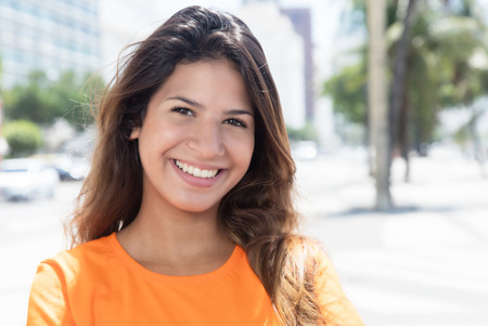 Beautiful caucasian woman in a orange shirt in the city