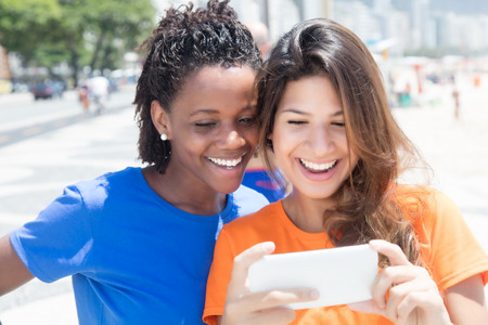 female friends: African american and caucasian looking at phone