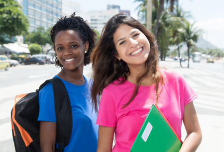 Lachende Afrikaanse Amerikaanse en Kaukasische student in stad