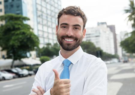 caritas felices: exitoso hombre de negocios con la barba y corbata azul en la ciudad