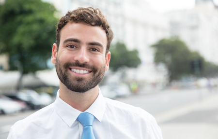 american banker: Laughing businessman with beard and blue tie in the city Stock Photo