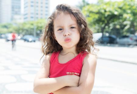 Moedig kind in een rood shirt buiten te kijken naar de camera