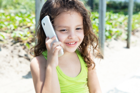 yellow shirt: Young child in a yellow shirt laughing at phone Stock Photo