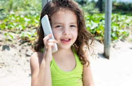 yellow shirt: Cute child in a yellow shirt laughing at phone Stock Photo