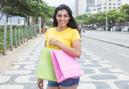 yellow shirt: Latin woman with yellow shirt and shopping bags in city