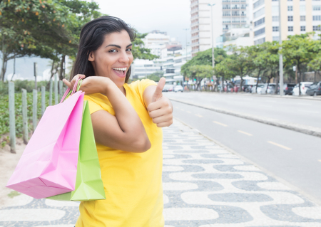 latina america: Latin woman with yellow shirt showing thumb after shopping in city Stock Photo