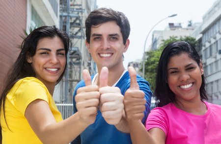 stylish hair: Group of three young people in colorful shirts showing thumbs Stock Photo