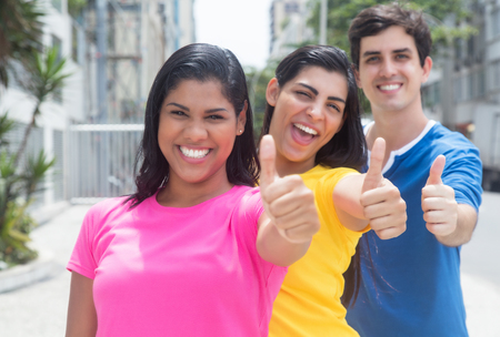 Trio jonge mensen in kleurrijke overhemden die zich in lijn bevinden en duimen tonen Stockfoto