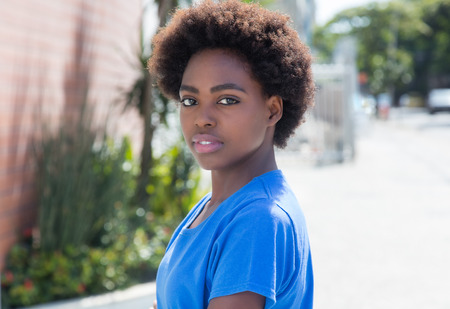 latin american: Shy african woman in a blue shirt outdoor in city with streets and buildings in the background Stock Photo