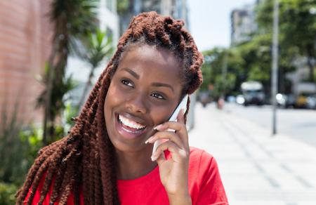 市内電話で笑ってドレッドヘアを持つアフリカの女性