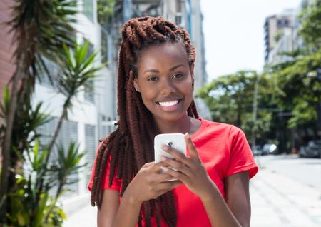 Afrikaanse vrouw met dreadlocks die bericht in de stad verzenden Stockfoto