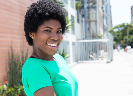 African woman in a green shirt in the city Stock Photo