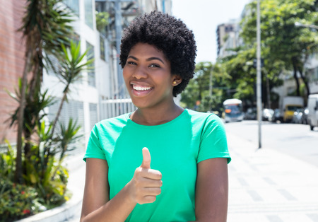 woman close up: Beautiful african woman in a green shirt in the city Stock Photo