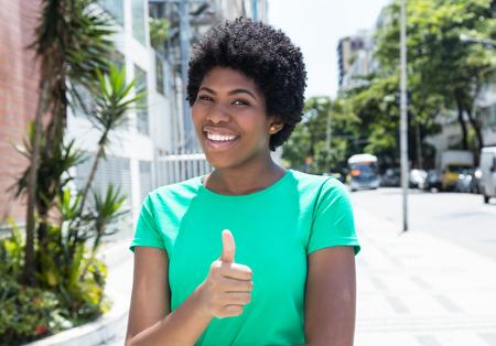 single woman: Mujer africana hermosa en una camisa verde de la ciudad